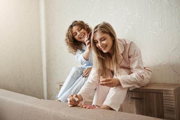 Das wochenende mit der schwester zu verbringen ist besser als alleine. charmante glückliche lockige frau im pyjama, die ihre freundhaare kämmt, während sie fingernägel auf füße malt, lacht und über das leben spricht