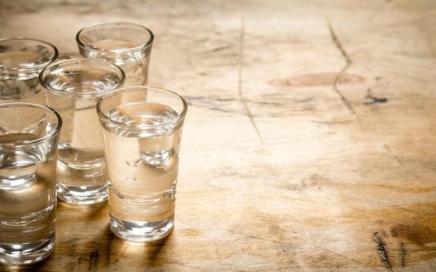 Das wodka-glas auf einem hölzernen hintergrund