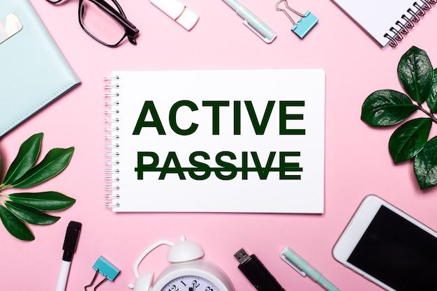 Das wort active steht in einem weißen notizbuch auf rosafarbenem hintergrund, umgeben von business-accessoires und grünen blättern.