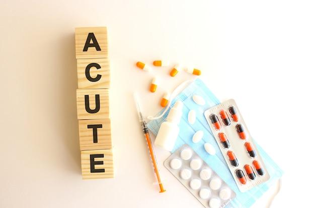 Das wort akut besteht aus holzwürfeln auf weißem grund mit medikamenten. medizinisches konzept.
