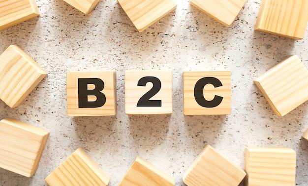 Das wort b2c besteht aus holzwürfeln mit buchstaben, draufsicht auf eine helle oberfläche.