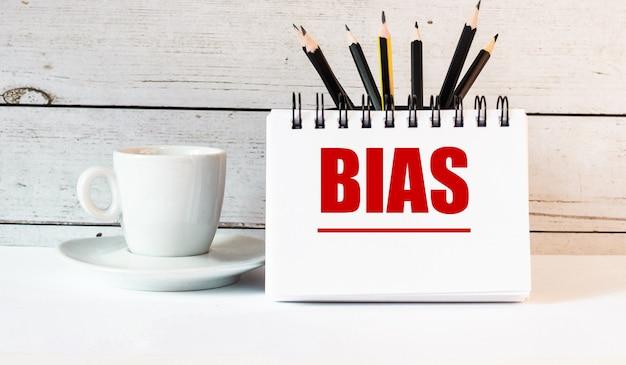 Das wort bias steht in einem weißen notizblock neben einer weißen tasse kaffee an einer hellen wand