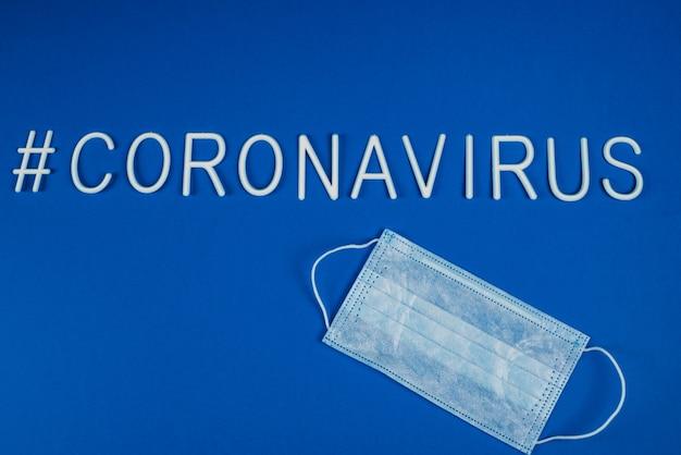Das wort coronavirus mit weißen buchstaben gelegt. atemschutzmaske neben dem wort coronavirus. nachrichten in sozialen netzwerken. hashtag. flache lage, copyspace