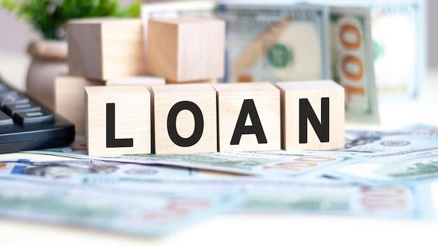 Das wort darlehen auf holzwürfeln, banknoten und taschenrechner. geschäfts- und finanzkonzept.
