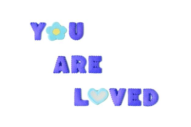 Das wort, das sie geliebt werden, buchstabierte mit klaren blauen alphabetplätzchen und -eibisch