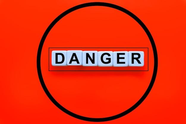 Das wort gefahr geschrieben auf würfel auf rotem grund. konzept der gefahr, bedrohung oder risikowarnung.