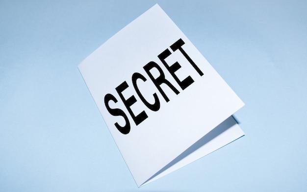 Das wort geheimnis ist auf weißem papier geschrieben, das in zwei hälften gefaltet ist