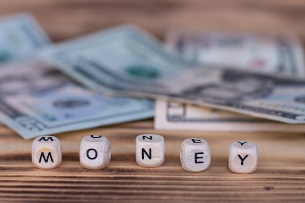 Das wort geld, mit buchstaben auf holzwürfeln auf einer oberfläche von dollarnoten ausgekleidet