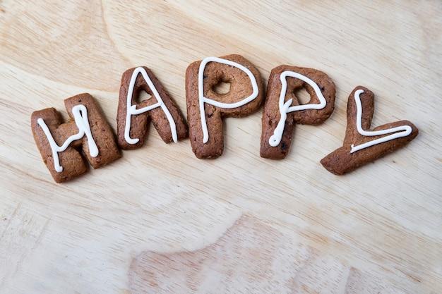 Das wort glücklich auf einem hölzernen hintergrund lebkuchenplätzchen mit zuckerguss hausgemachte kuchen