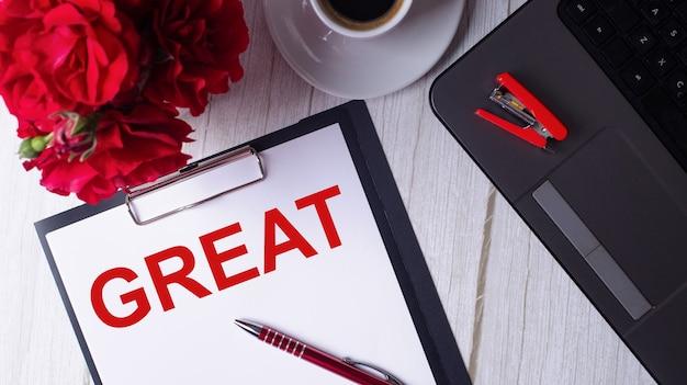Das wort gross ist in rot auf einem weißen notizblock neben einem laptop, kaffee, roten rosen und einem stift geschrieben.
