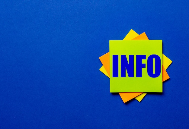 Das wort info steht auf hellen aufklebern auf einer blauen oberfläche.