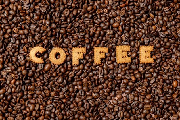 Das wort kaffee aus keksbuchstaben auf einem dunklen kaffeebohnenhintergrund