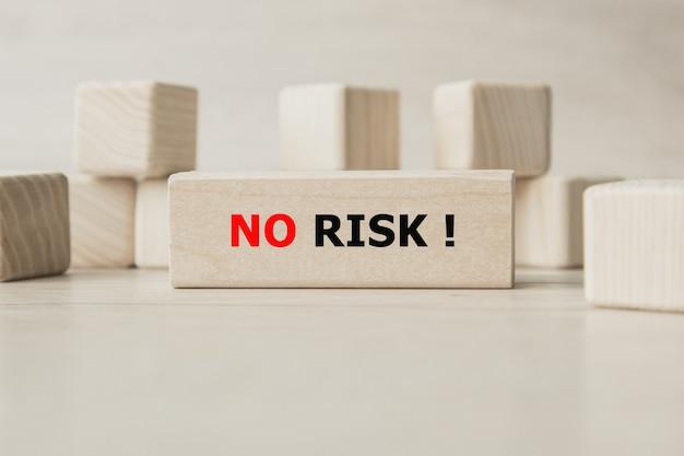 Das wort kein risiko steht auf einer holzwürfelstruktur. würfel auf einem hellen tisch.