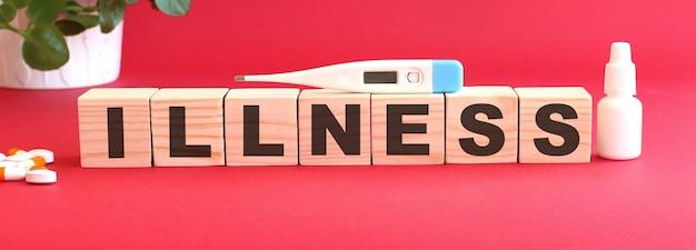 Das wort krankheit besteht aus holzwürfeln auf rotem grund mit medikamenten.