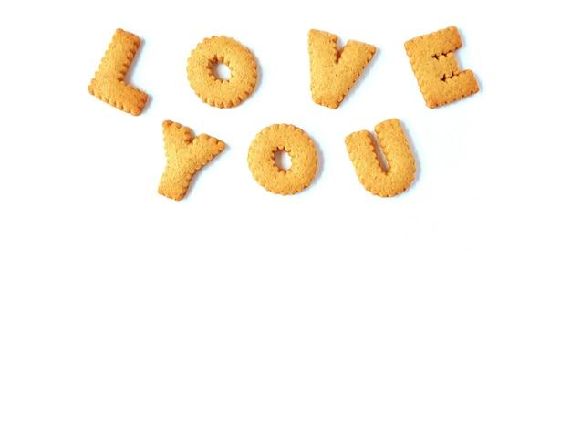 Das wort liebe dich geschrieben mit alphabet formte die kekse, lokalisiert auf weißem hintergrund