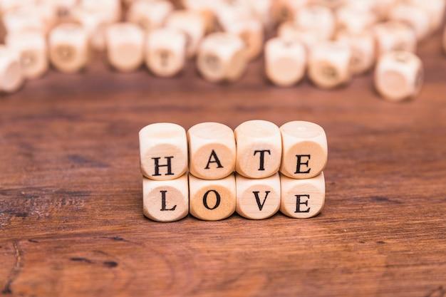 Das wort liebe und hass vereinbarte mit hölzernen würfeln