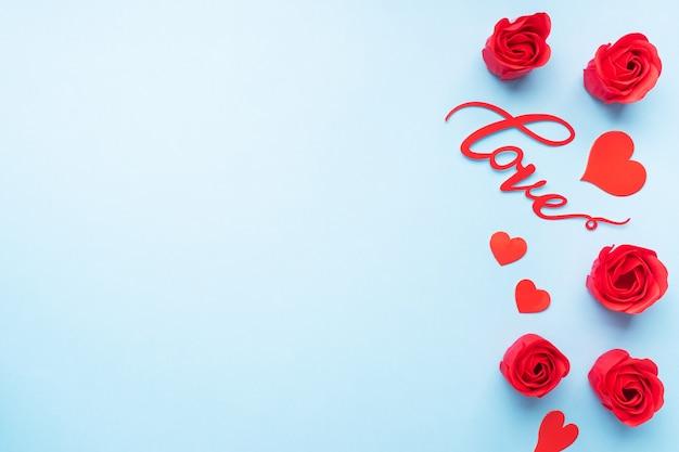 Das wort liebe und rote herzen rosen auf einem blauen hintergrund, draufsicht. valentinstag. flach liegen.
