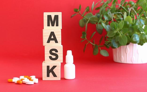 Das wort maske besteht aus holzwürfeln auf rotem grund mit medikamenten.