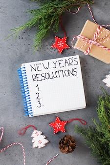 Das wort neujahrsauflösung in einem weißen notizbuch auf einem grauen neujahrshintergrund-kopierraum geschrieben