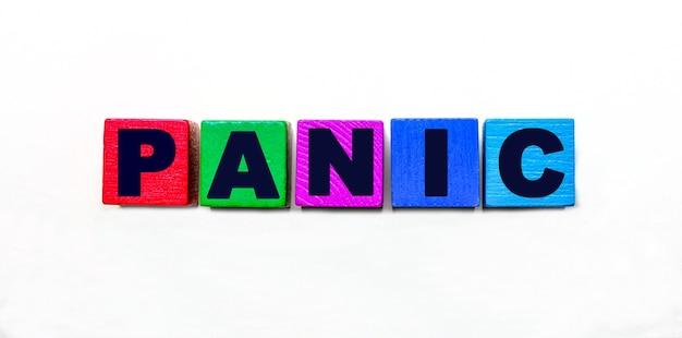 Das wort panik steht auf bunten würfeln auf hellem hintergrund