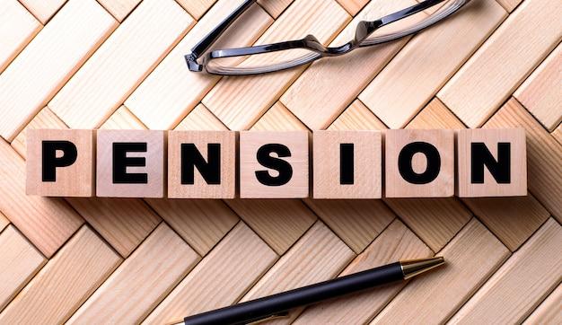 Das wort pension steht auf holzwürfeln auf einer holzoberfläche neben einem stift und einer brille.