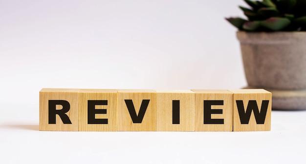 Das wort review auf holzwürfeln auf einem hellen hintergrund nahe einer blume in einem topf