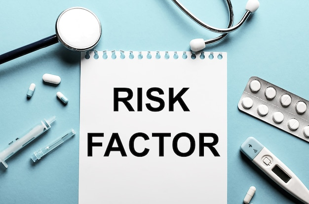 Das wort risikofaktor geschrieben auf einem weißen notizblock an einer blauen wand in der nähe eines stethoskops, einer spritze, eines elektronischen thermometers und von pillen. medizinisches konzept