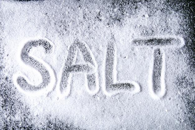 Das wort salz wird auf kleine salzkristalle geschrieben, die auf einem schwarzen tisch verstreut sind.