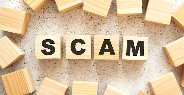 Das wort scam besteht aus holzwürfeln mit buchstaben, draufsicht auf hellem hintergrund.
