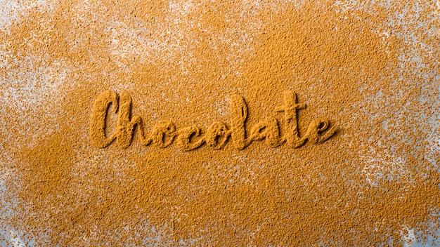 Das wort schokolade ist mit schönen kakaobuchstaben auf dem hintergrund von kakaopulver ausgekleidet