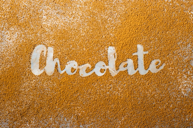 Das wort schokolade wird in weiß auf dem hintergrund von kakaopulver gedruckt