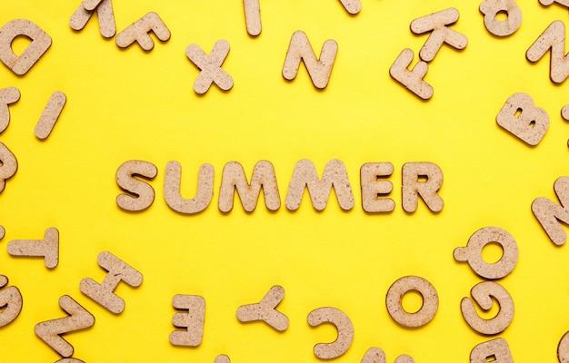 Das wort sommer unter holzbuchstaben auf gelber oberfläche.