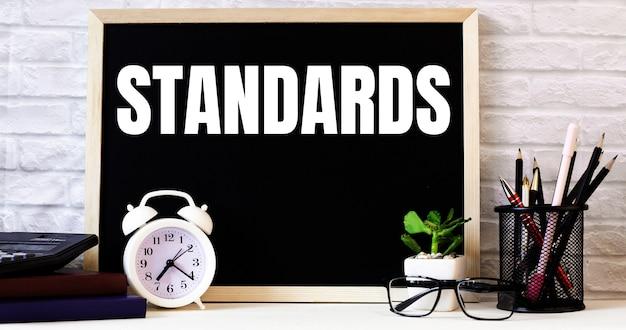 Das wort standards steht an der tafel neben dem weißen wecker, den gläsern, der topfpflanze und den stiften in einem ständer.