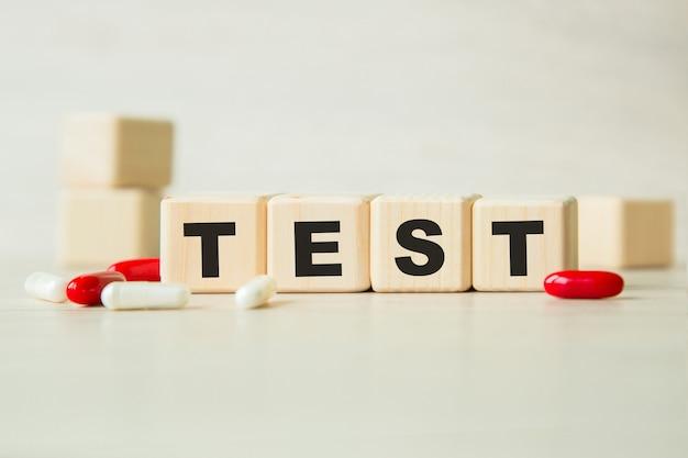 Das wort test steht auf einer holzwürfelstruktur mit tafeln