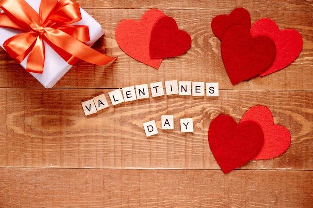 Das wort valentinstag. liebe auf holzklötzen auf natürlichem hintergrund. thema der liebe, des herzens und des geschenks.