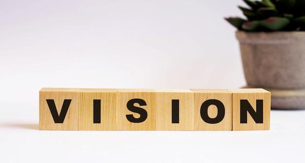 Das wort vision auf holzwürfeln auf hellem hintergrund in der nähe einer blume in einem topf. defokussieren