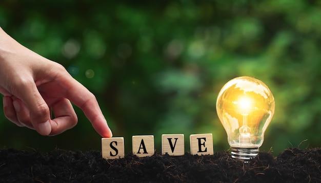 Das wort von save auf holzwürfeln mit glühbirne mit handkonzeptidee, die energiesparlampe