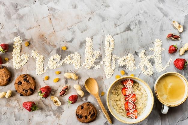 Das wortfrühstück wird auf einen grauen hintergrund des hafermehls geschrieben
