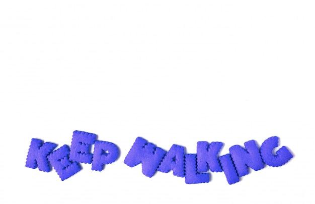 Das zitat keep walking ist mit blauen, alphabetisch geformten keksen geschrieben
