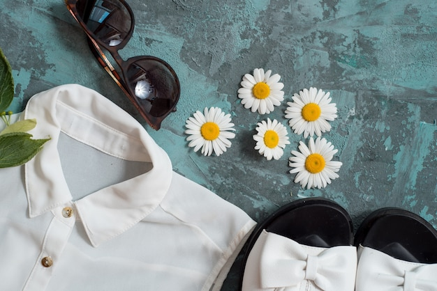 Das zubehör der flachen lagestrandfrauen: strohhut, armbänder, ledersandalen, sonnenbrillen, perlen und seesterne auf blauer tabelle