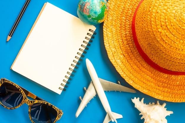 Das zubehör des reisenden, obenliegende ansicht von wesentlichen ferieneinzelteilen, reisehintergrund.