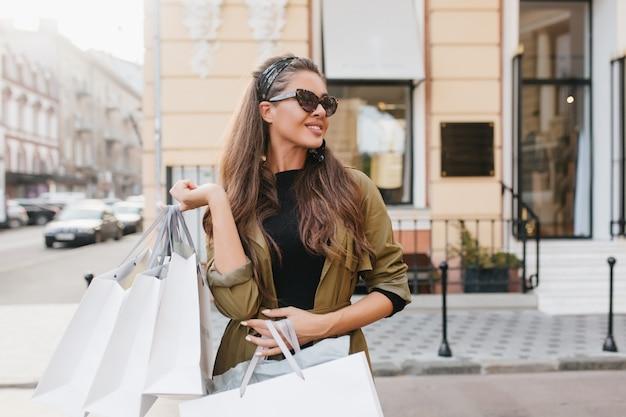Das zufriedene lateinamerikanische weibliche model trägt einen eleganten mantel, der das einkaufen im herbstmorgen genießt