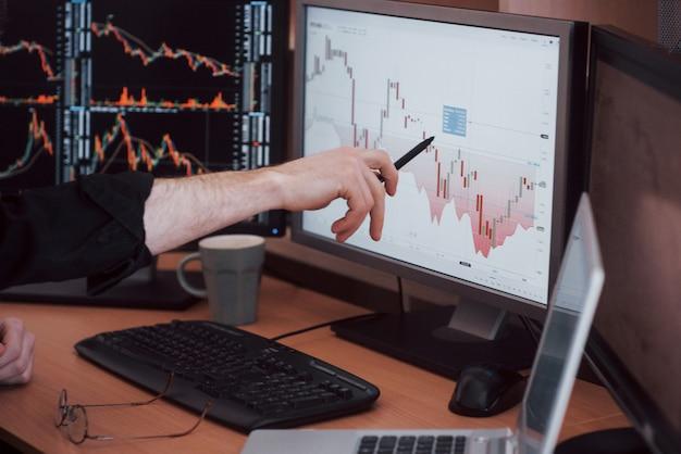 Daten analysieren. die nahaufnahme des jungen geschäftsmannes zeigend bezüglich der daten stellte sich im diagramm mit stift beim arbeiten im kreativen büro dar