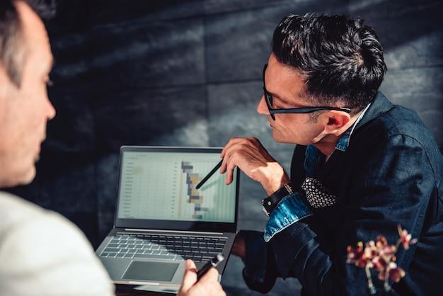 Datenanalytiker, der auf bericht über laptop zeigt