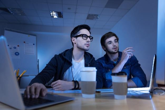 Datenprivatsphäre. intelligentes genie, gutaussehende hacker, die den laptop benutzen und persönliche daten stehlen, während sie ein cyber-verbrechen begehen