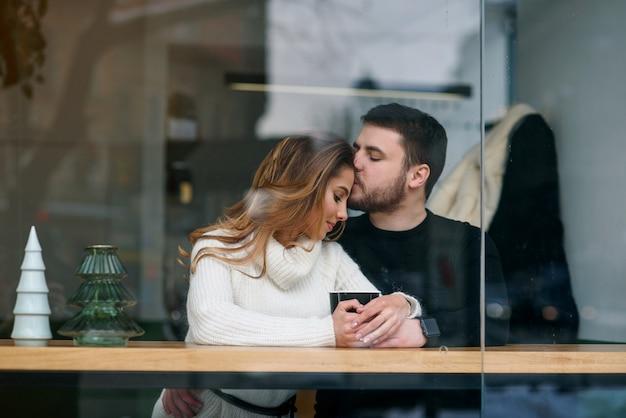 Dating in einem café. schönes lächelndes mädchen mit ihrem freund, der in einem café genießt im kaffee und im gespräch sitzt.