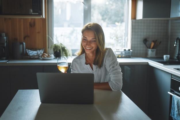Dating online-konzept. glückliche junge frau mit glaswein, der durch soziales netzwerk spricht, das zu hause in der küche sitzt