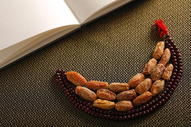 Dattel trägt mit perlen eines islamischen gebets auf einem künstlerischen hintergrund früchte