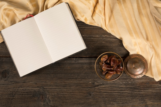 Dattelfrucht in der schüssel mit leerem notizbuch