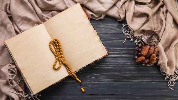 Dattelfrucht mit leerem notizbuch und perlen